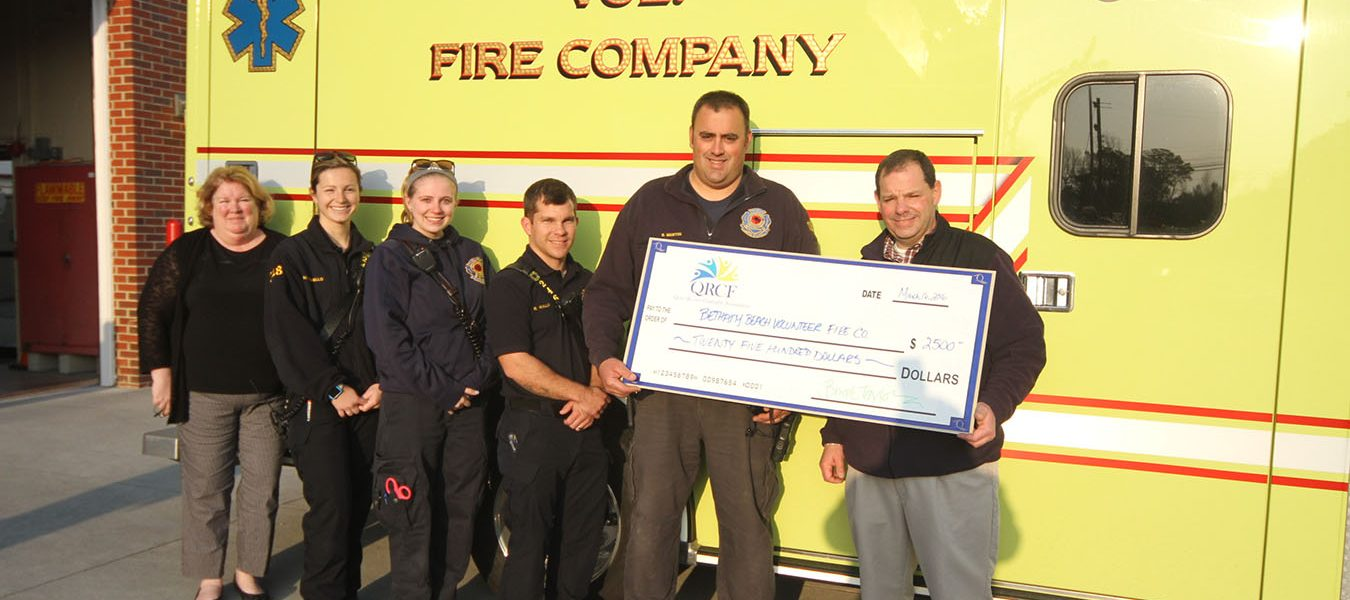 A large check for $2500 being held with firefighters