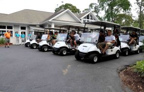 A fleet of golf carts filled with golfers in a parking lot.