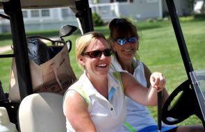 Two women smiling while driving a golf cart.