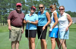 Four women and one man smiling while on a golf course holding golf clubs