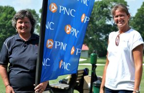 Women posing outdoors for photo with one holding a flag with the PNC logo