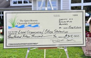 Outdoor photo of a giant check for $315,000 towards local organizations and college scholarships.