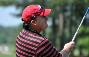 Male golfer mid-swing wearing red hat and red and black striped shirt.