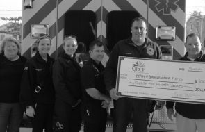 A giant check being held outside behind an ambulance in grayscale