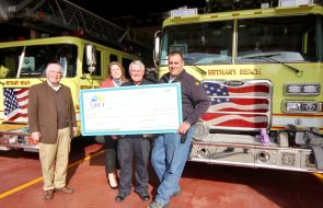 Three people holding up a check in front of two yellow firetrucks
