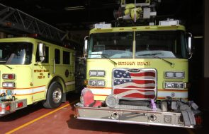 Two yellow fire trucks with white stripes in fire station