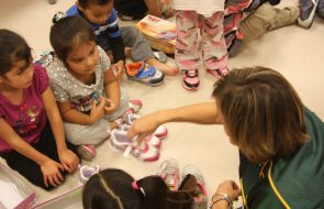 Woman handing out shoes to the little girls