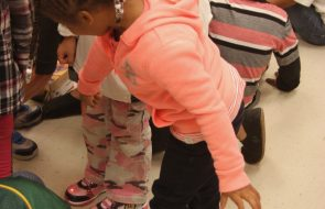 Little girl pointing at new shoes other girl is wearing