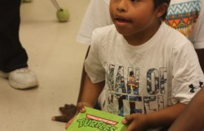 A kid holding a Ninja Turtle Shoebox