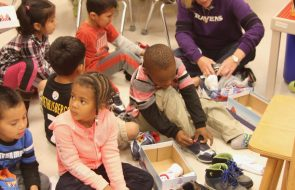 Kids in a classroom trying on new shoes