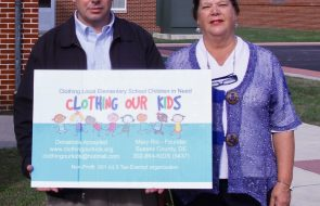Man and woman holding up a sign for Clothing our Kids