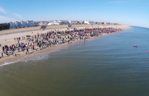 People gathered on the beach in front of some condos