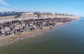 A large group of people waiting on the beach