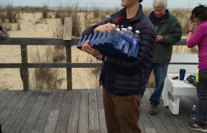 A kid holding a case of water and handing it out to people