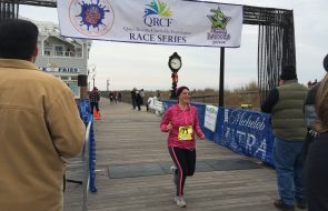 A tired woman makes her way across the finish line