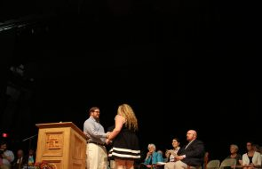 Girl shaking hands with guy as she accepts an award