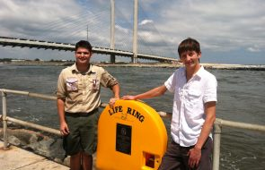 Two eagle scouts in front of a life ring