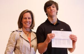 A teenager with a black shirt holding up his scholarship