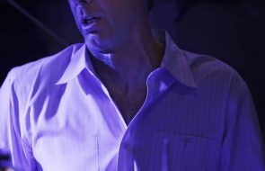 A man under a blue light sweating