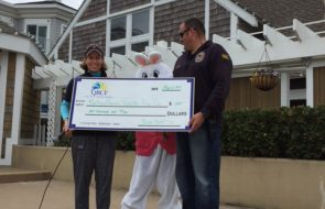 A giant check being held by two people with a bunny suited person